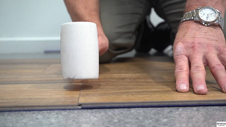 Close up showing hammer tapping floor