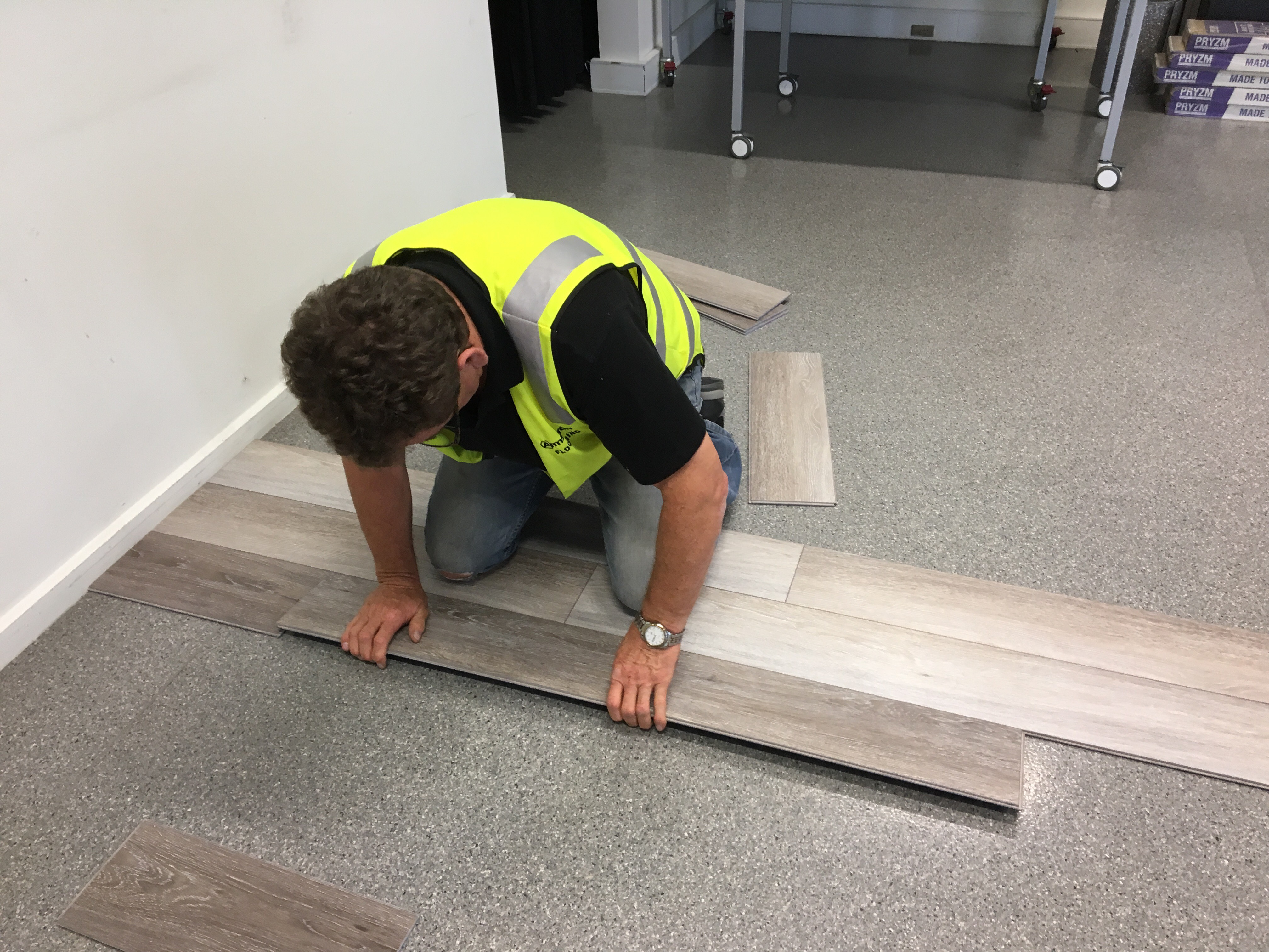 Man installing hybrid rigid core flooring